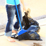 Girl Cleaning Up With Broom and Trash Bags